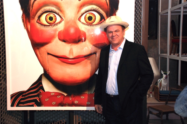 "John C. Reilly poses with the portrait used on the ""Talking Heads"" cover. Photo © R-ROLL/MRPI, 2013. All rights reserved."