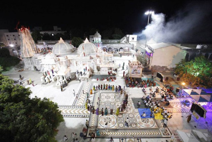 This temple in the north of Gujarat is entirely unknown. On the eighth day of Navratri,  women perform the ritual circle dance as the men are watching. In the background pilgrims are making offerings in the temple, that is decorated for the celebration with thousands of LED lights. On the upper right corner holy smoke fills the temple area, from a fire-temple in which Ayurvedic ingredients are burnt in a huge lot. After long negotiations with the local priests, we were allowed to climb the temple roof  and gates, of this ancient temple. This temple and celebration has never been documented to this extend before.