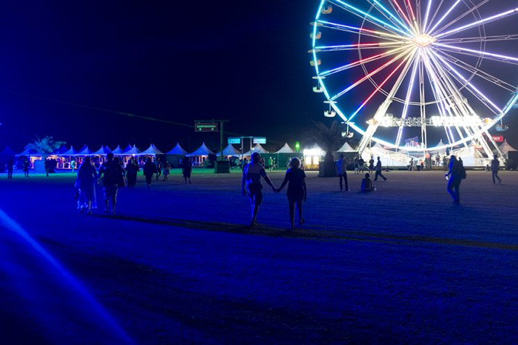 NDIO, CA - Oct. 9: A couple walks holding hands through the festival grounds during the final night of musical performances of the first weekend of Desert Trip Music Festival, which features bands Bob Dylan, The Rolling Stones, Paul McCartney, Neil Young, The Who and Roger Waters, in Indio, California October 9, 2016. Photo by Brinson+Banks