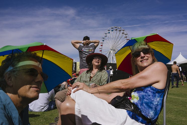 INDIO, CA - Oct. 7: Greetings from just outside the gates of Desert Trip, in Indio, California, where fans are lining up to get in to the three-day music festival with Bob Dylan, The Rolling Stones, Paul McCartney, Neil Young, The Who and Roger Waters. Mark Portman (left) and his wife Jan Simmons (right), of Oregon, and longtime friend Maggie Sichel-Pinatelli, of California, brave the 95 degrees today and have seen hundreds of concerts together. Simmons was the assistant tour manager for the Grateful Dead. Photo by Brinson+Banks Model Release: Yes
