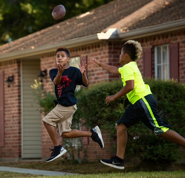 BEAUMONT, TX - NOVEMBER 01: Jaelun Parkerson plays catch with his dad and brothers and friend Kyle Gillroy front of his home. Jealun is a member of the Beaumont Bulls senior youth football team from Beaumont, TX. (Walter Iooss for ESPN)