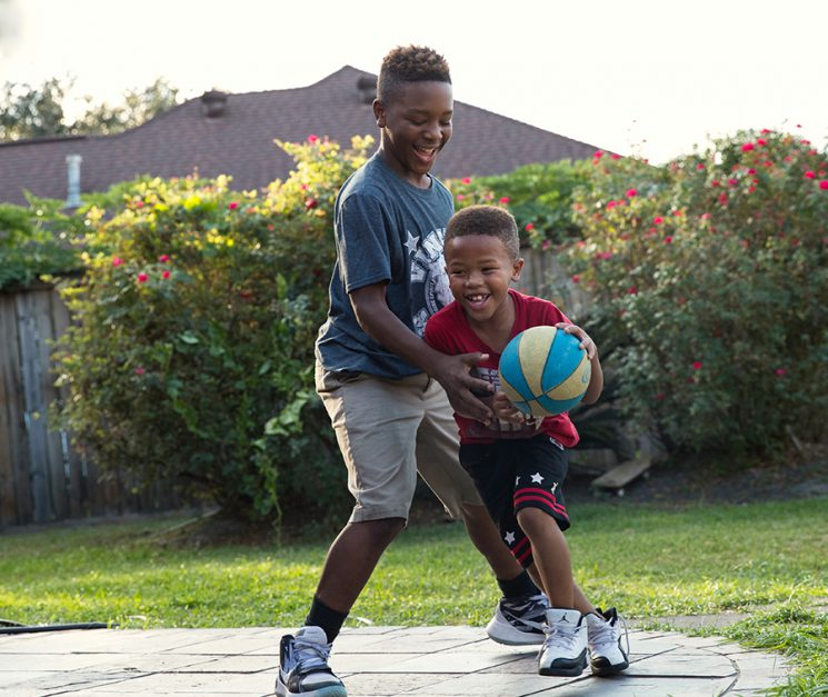 BEAUMONT, TX - NOVEMBER 01: Larry Brooks of the Beaumont Bulls senior youth football team plays basketball with his brothers and sister in his back yard in Beaumont, TX. (Walter Iooss for ESPN)